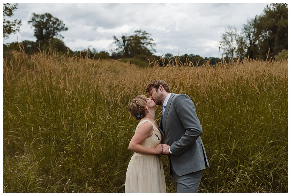 Bride and Groom kissing in field in late summer at red Barn Studios in Chehalis, WA