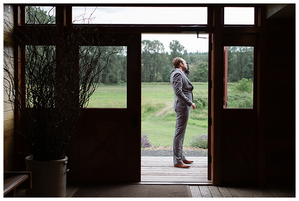 Groom waiting for bride before wedding near lavender fields at Red Barn Studios in Chehalis, WA