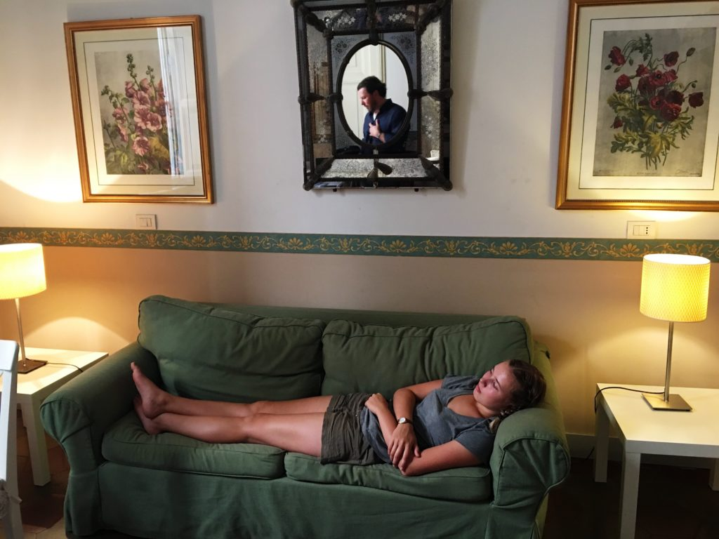 Girl lies on green couch and man is reflected in mirror above her head with floral framed prints on wither side