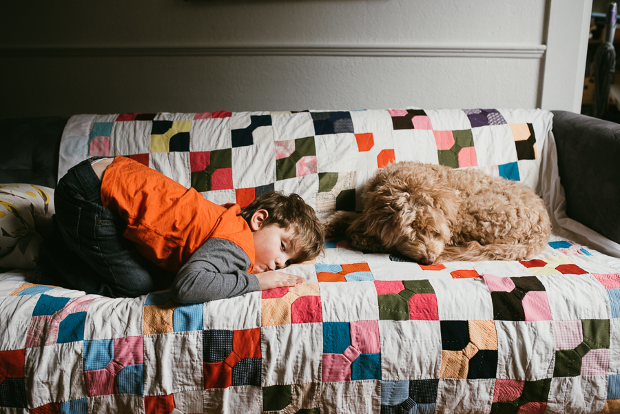 boy and dog on couch covered with bright quilt by Jessica Uhler Photography