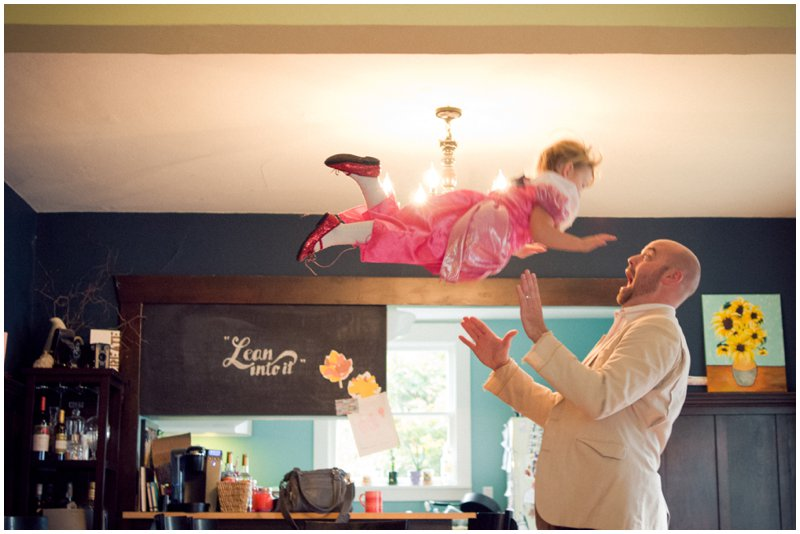 dad throws his little girl up on the air and catches her. She is wearing a pink dress and red sparkly shoes