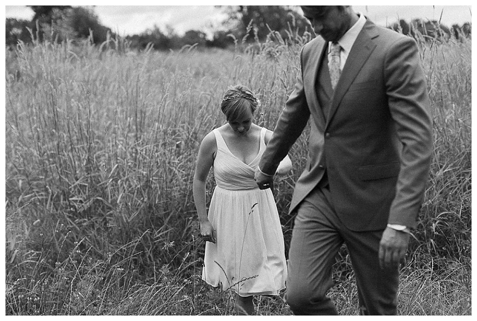 black and white picture of bride and grromholding hands and walking in field at Red Barn Studios, Chehalis, WA