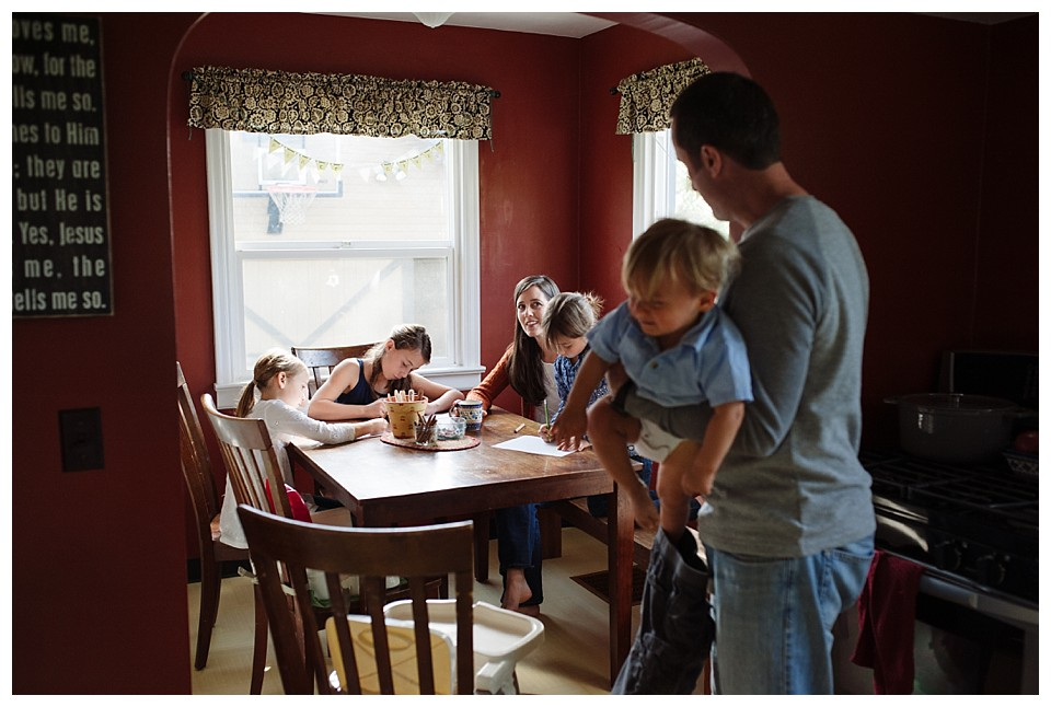 mom and kids doing crafts at a kitchen table while dad looks on holding a baby