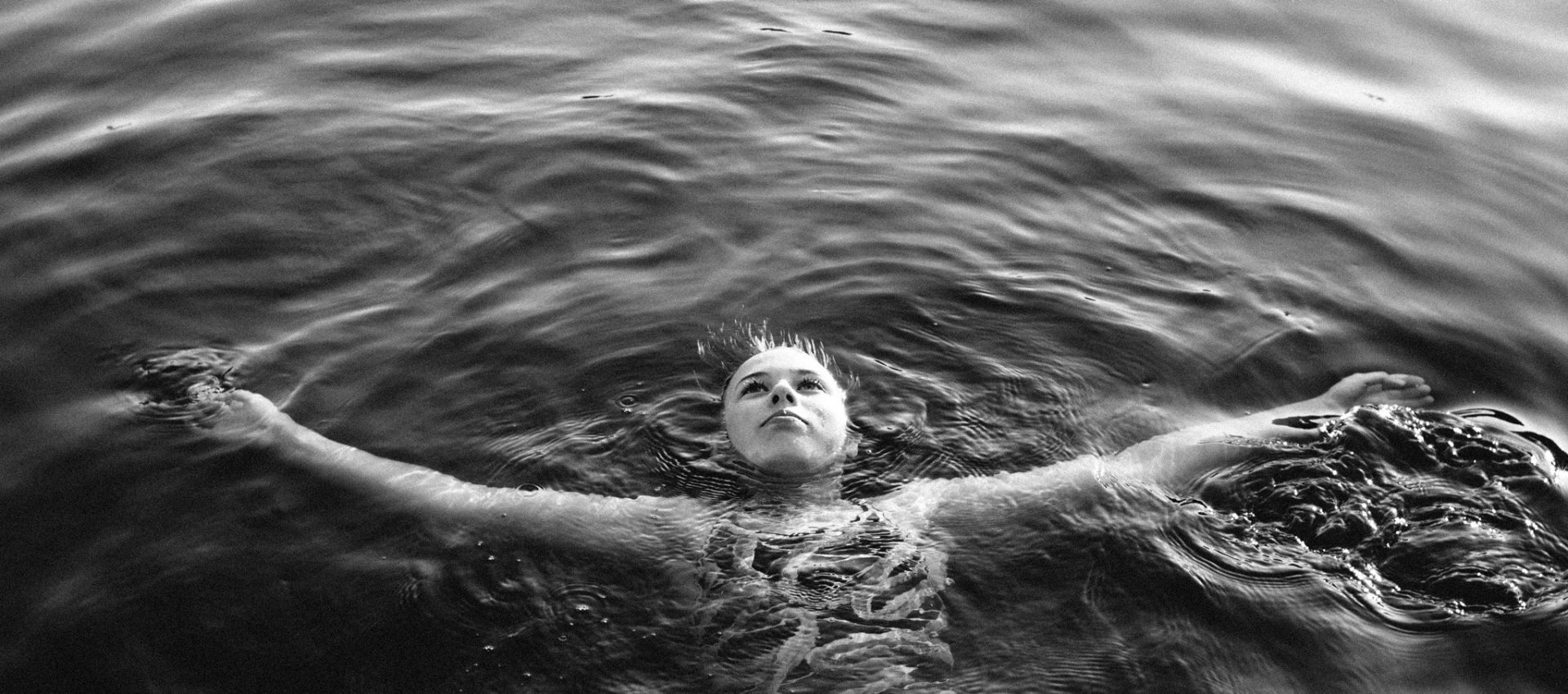 Black and white image of girl floating in lake with outstretched arms by Seattle area family photographer Jessica Uhler