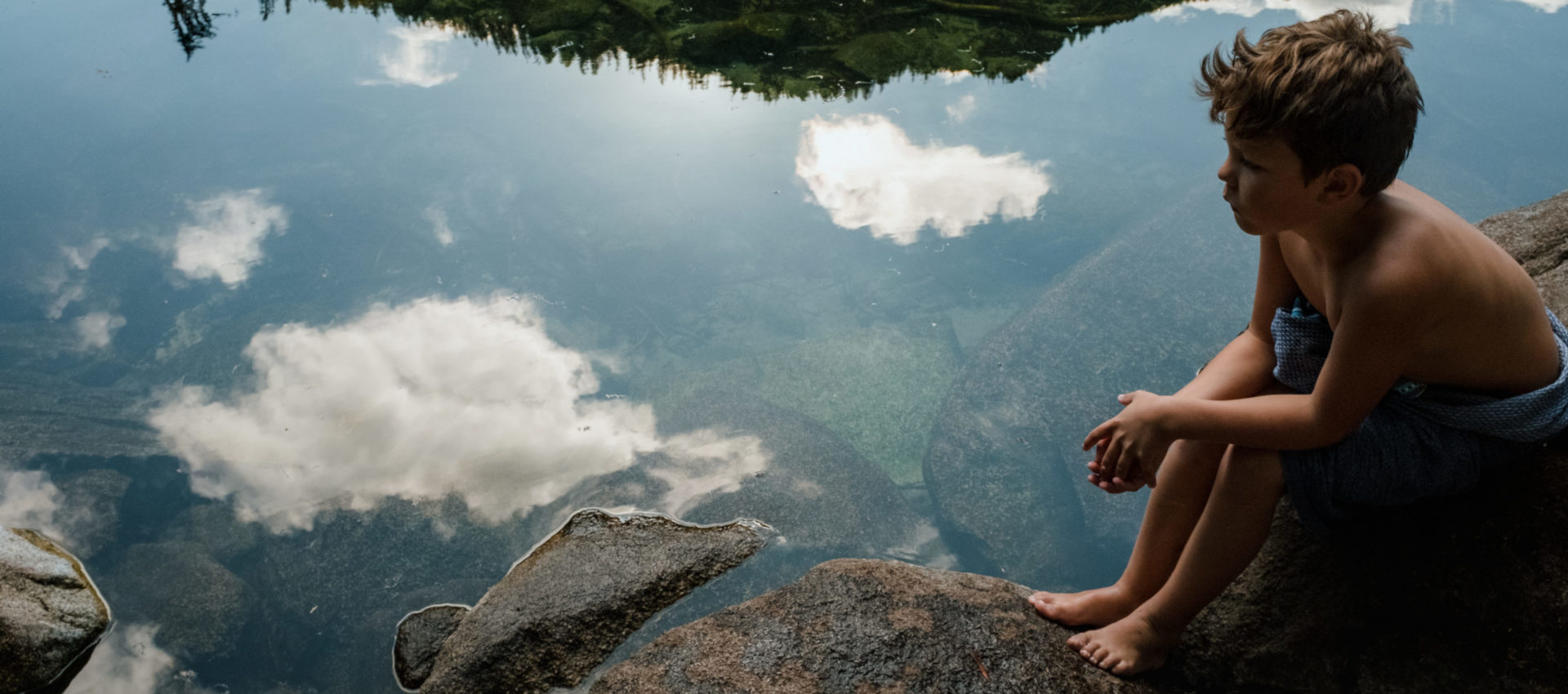 young boy sits by the water where clouds and mountains are reflected